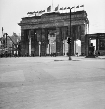 The partially restored Brandenburg Gate in Berlin decorated with flags, banners and slogans promoting a Festival of German Youth, 1 May 1950.