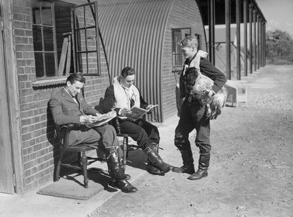 Pilots of No. 19 Squadron relax between sorties outside their crew room at Manor Farm, Fowlmere, near Duxford, September 1940. Left to right: Pilot Officer W Cunningham, Sub-Lieutenant A G Blake of the Fleet Air Arm and Flying Officer F N Brinsden.