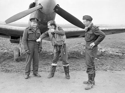 Flight Lieutenant J Pattison of No. 485 Squadron RNZAF graphically recounts a combat to Squadron Leader 'Reg' Grant (left), and Flight Lieutenant R Baker (right), in front of a Spitfire at Westhampnett, 21 January 1943.