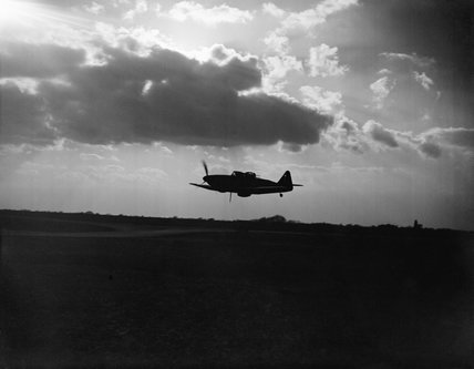Boulton Paul Defiant Mk I night-fighter of No. 264 Squadron RAF, silhouetted against the clouds during a low-level pass over its base at Biggin Hill, Kent, April 1941.
