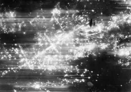 A photograph taken from 19,000 feet during an RAF raid on Hannover on the night of 8/9 October 1943. An Avro Lancaster can be seen silhouetted against the fires below.