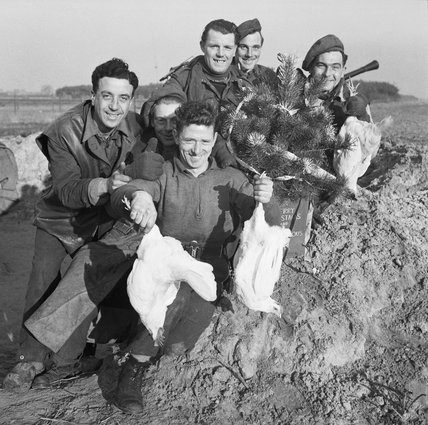 A group of cheerful men from the Royal Artillery display chickens acquired for their Christmas dinner, Venray in Holland, 24 December 1944.