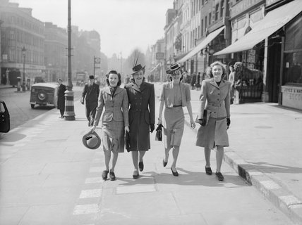 Four young ladies enjoy a stroll in the Spring sunshine along a shopping street in the West End of London during 1941.
