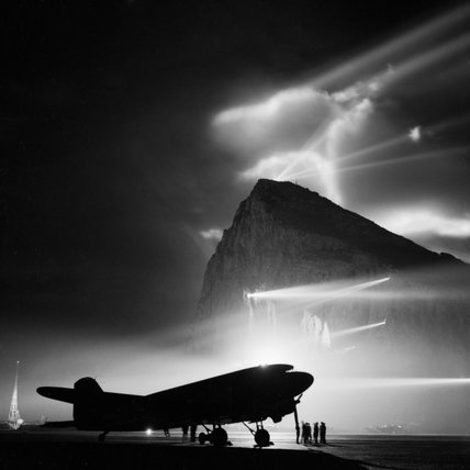 A Douglas Dakota of BOAC at Gibraltar, silhouetted by searchlights on the Rock.