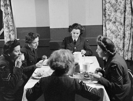 Members of the Women's Auxiliary Air Force (WAAF) enjoy a meal at a RAF base in Britain during 1942.