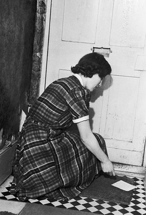 Mrs J London collects a letter from the front door mat of her home in Dugdale Street, Camberwell, London, in early 1942. The photograph is one of a series to illustrate the salvage of paper.