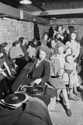 A young woman plays a gramophone in an air raid shelter in north London during 1940.