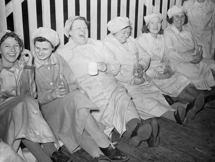 Six women munitions workers enjoy a cup of tea during their break.