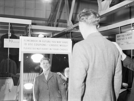 An aircrew training cadet who volunteered to take part in a demobilisation rehearsal, checks out the fit of his 'demob suit' at a civilian clothing centre in Wembley, 17 October 1944 .