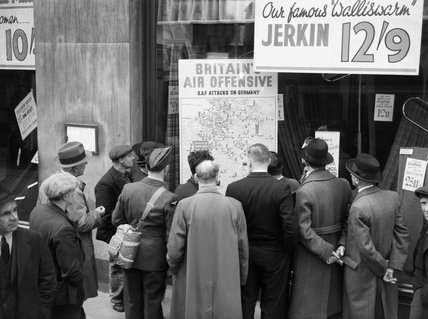A British airman is amongst a group of civilians crowded around the window of a shop in Holborn, London, to look at a map illustrating how the RAF is striking back at Germany during 1940.