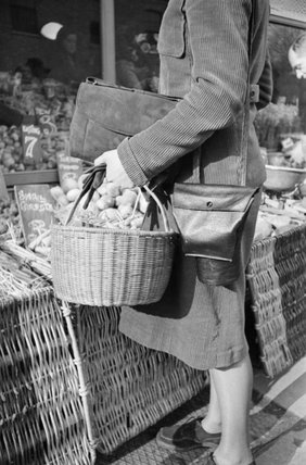 A housewife carrying shopping basket and gas mask container shops at a greengrocers in London during 1941.