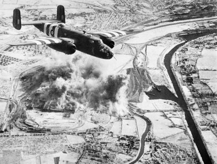 A North American Mitchell Mk II of No. 320 (Dutch) Squadron flying over the Colombelles steel works near Caen in Normandy, during an attack on 22 June 1944.