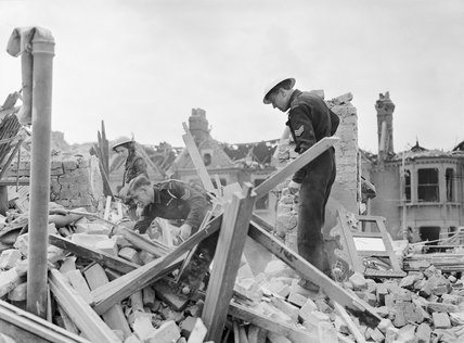 Civil Defence wardens and a member of the American Ambulance Great Britain search amongst rubble for salvageable items following a V1 Flying Bomb strike in Upper Norwood, south London during 1944.