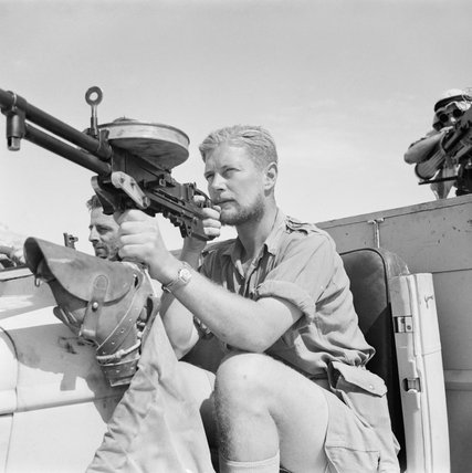 A member of a Long Range Desert Group (LRDG) patrol poses with a Vickers 'K' Gas-operated machine gun on a Chevrolet 30-cwt truck, May 1942.