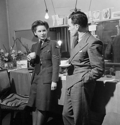 Actress Muriel Pavlow chats with casting director Bob Lennard of the Associated British Picture Corporation in her dressing room at the Globe Theatre, London during 1945.