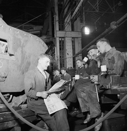 Factory workers on a lunch break beside the Matilda II tank they are constructing, 1942.