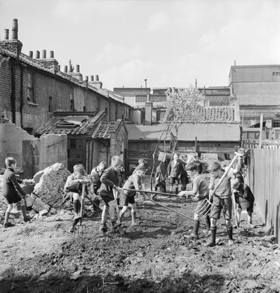 A group of boys set to work creating an allotment on a bomb site in London during 1942.
