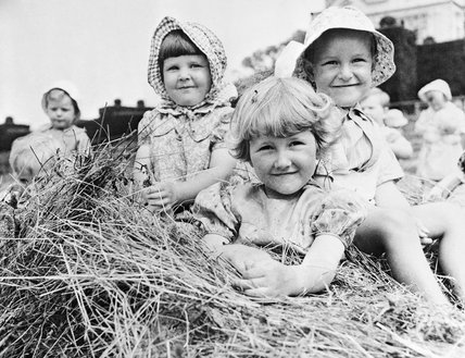 A group of children sitting on a large pile of hay outside Chapel Cleeve Nursery in Washford, Somerset during 1942.