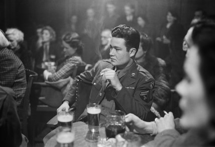 An American soldier listening to a speaker at a debating society meeting in the Freemason's Arms pub in Hampstead, London, during 1945.