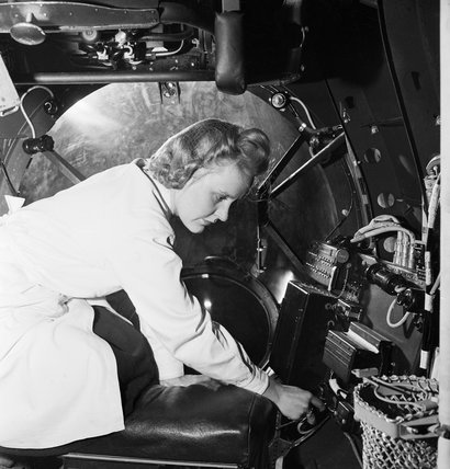 A female electrical worker fitting the bomb aimers switch into the half completed fuselage of an Avro Lancaster.