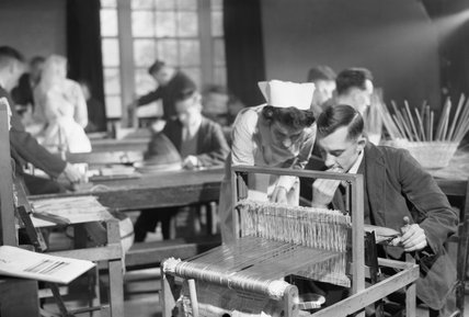 A nurse assists a convalescing soldier as he works on a piece of weaving as part of his rehabilitation programme at Mill Hill Hospital in 1942.
