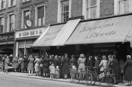Women and children queue to buy vegetables from a greengrocers in London during 1945.