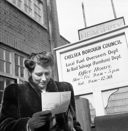 Marcelle Lestrange looks at her permit for Utility furniture which she has just received from Chelsea Borough Council in March 1943.
