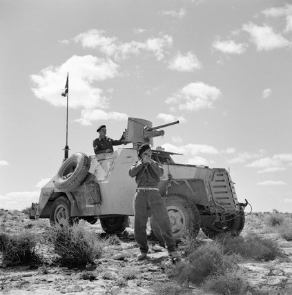 A South African Marmon-Herrington armoured car crew stops to take a compass bearing during a patrol in the Western Desert, 13 April 1942.