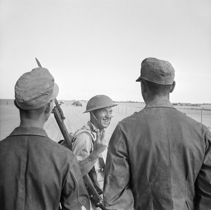 A British soldier gives a V-for-Victory sign to German prisoners captured at El Alamein, 26 October 1942.