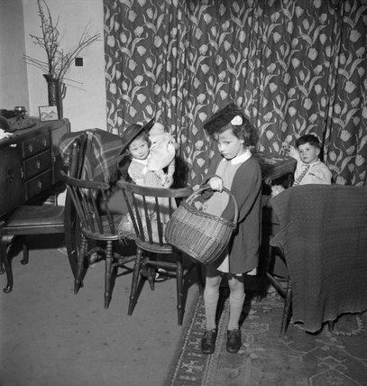 Doreen Buckner and her brother and sister play at shopping in their London home during the night-time 'Blackout' in 1943.