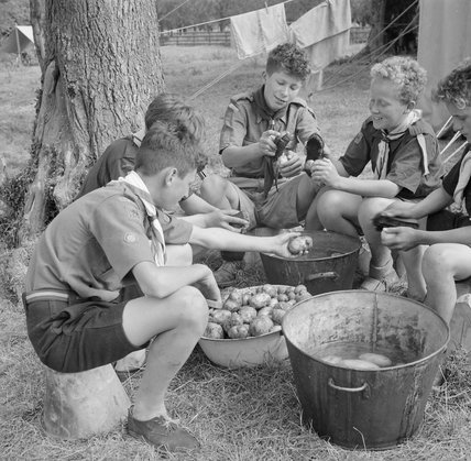 Boy Scouts scrub potatoes ready for the evening meal at a fruit-picking camp near Cambridge in 1943.