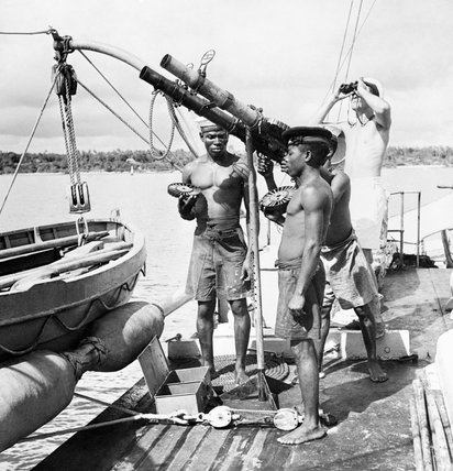 Men of the Kenyan Royal Naval Volunteer Reserve man a Lewis gun on board the minesweeper HMS ONYX, while on a local river patrol, October 1942.