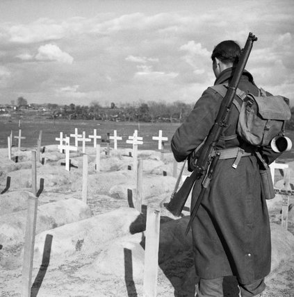 Private Phillip Johnson of the 2/6th Queen's Regiment inspects British graves at Anzio, Italy, 1 March 1944.