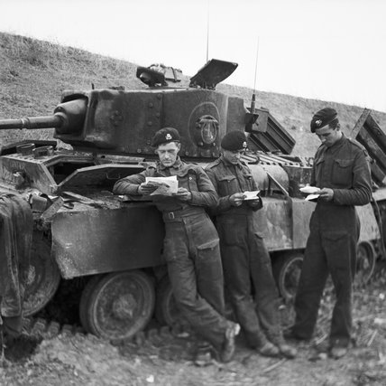 A Valentine tank crew in Tunisia reading letters by the side of their vehicle, December 1942.