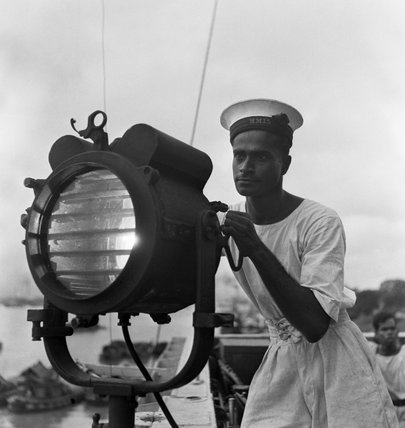 Cecil Beaton portrait of an Indian naval rating operating a signal lamp on the sloop SUTLEJ at the Royal Indian Naval Station at Calcutta, 1944.