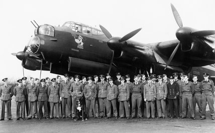Aircrew of No. 106 Squadron RAF gather in front of the Avro Lancaster flown by the Squadron CO, Wing Commander Guy Gibson (centre, to right of dog), to mark the completion of his first tour of operations, Syerston in Nottinghamshire, March 1943.