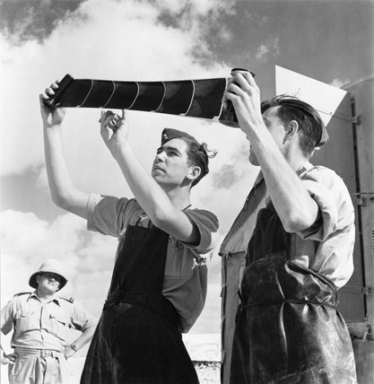 RAF photographers inspect a developed reconnaissance film at a landing ground in Egypt, September 1941.