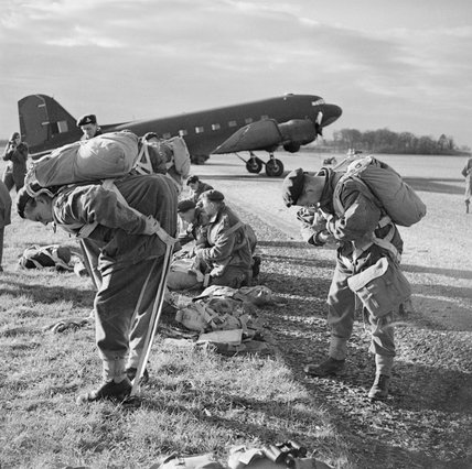 British paratroops fitting their parachute harnesses before entering a Dakota during a large-scale airborne forces exercise, 22 April 1944.