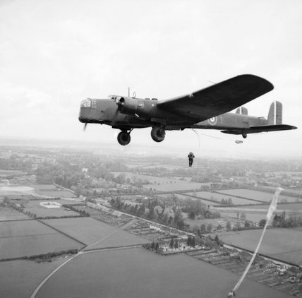 Parachute troops jump from a Whitley bomber during a demonstration for the King near Windsor, 25 May 1941.