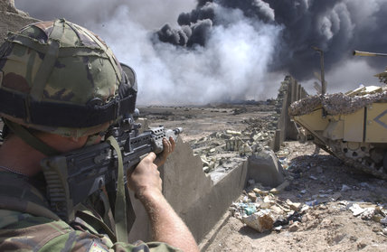 A soldier of 1st Battalion, The Irish Guards keeps a watch on enemy positions as Royal Engineers cap a burning oil well within the city of Basra in Iraq, 3 April 2003.