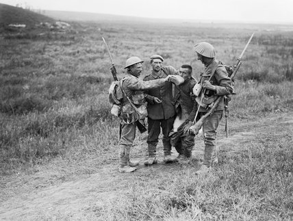 British infantrymen give a helping hand to wounded German prisoners near La Boisselle during the Battle of the Somme, 3 July 1916.
