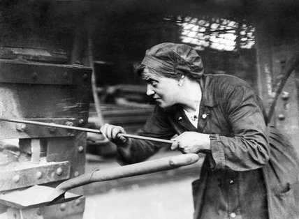 A female riveter's mate, heating rivets in a furnace at the shipyard of Swan, Hunter & Wigham Richardson, Ltd. in Newcastle during the First World War.