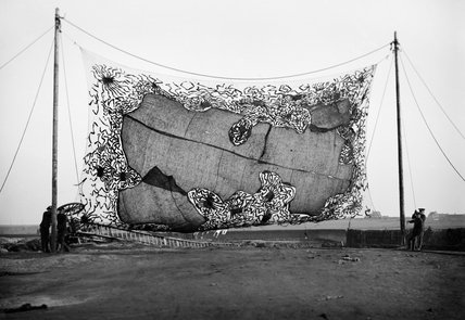 A camouflage screen produced during the First World War from canvas and fish netting to simulate broken ground and grass cover.