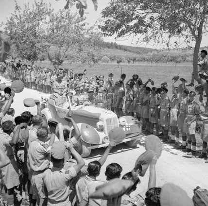 King George VI is driven past cheering Indian troops on his way to a ceremony to invest Sepoy Kamal Ram with the Victoria Cross, Italy, 26 July 1944.