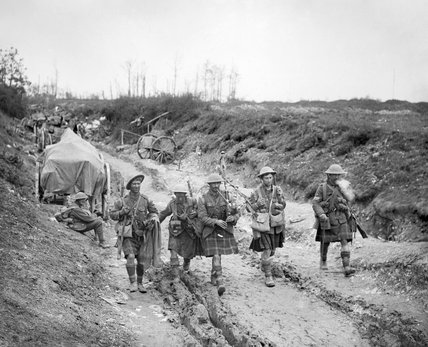 During the Battle of the Somme, a piper of the 7th Battalion, Seaforth Highlanders leads four men of 26th Brigade down a sunken road after the attack on Longueval, 14 July 1916.