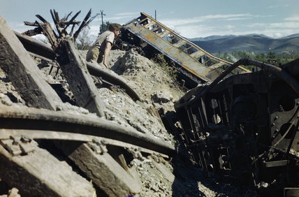 A British soldier inspects the wreckage of a goods train destroyed in Allied air raids on the Cortona-Arezzo railway line in Italy, July 1944.