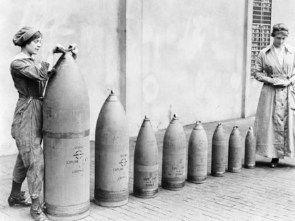 Two women munitions workers stand beside shells produced at National Shell Filling Factory, Nottinghamshire.