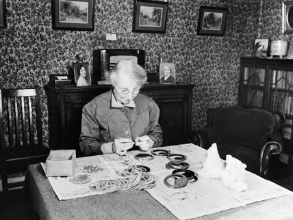 A female 'outworker' inserting glass into instrument covers at a table in her own home during 1943.