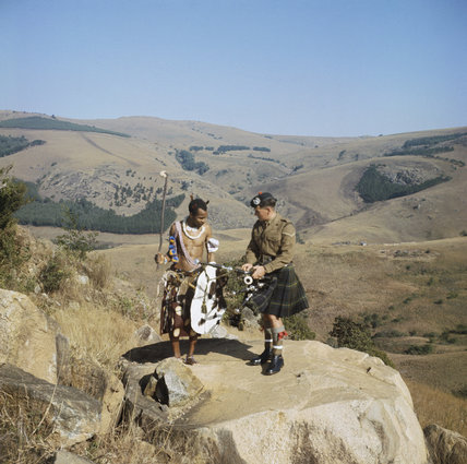 A piper of the 1st Battalion, The Gordon Highlanders, meeting a Swazi warrior in full war dress, East Africa, August 1963.