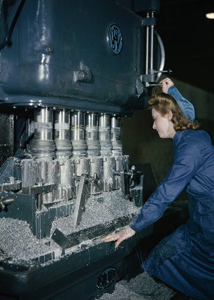A woman war worker machining pistons for a Rolls Royce aero engine.